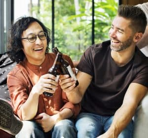 A woman and man clink glasses while laughing
