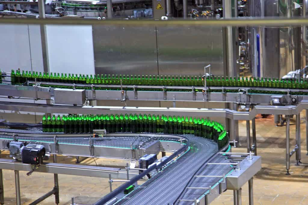 Bottles getting filled on conveyor belt