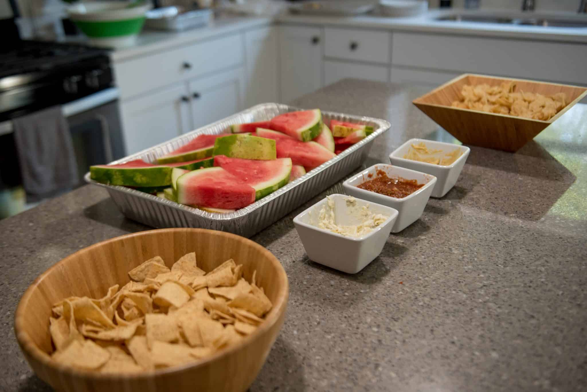 Chips and dip next to a bowl of watermelon on a countertop