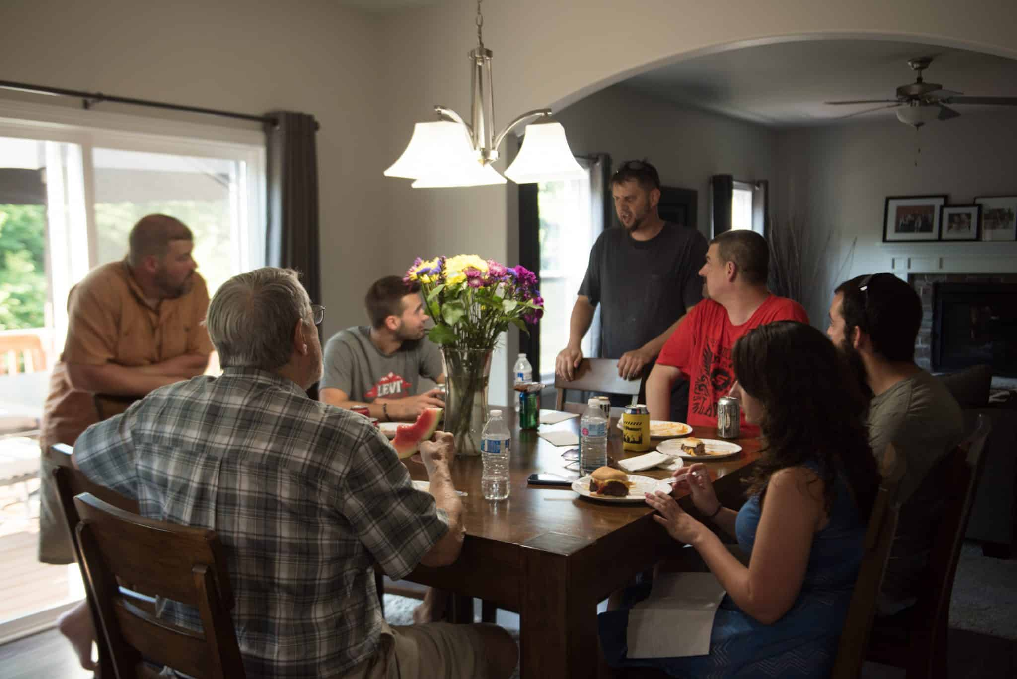 Apex employees and family members chatting at a dinner table