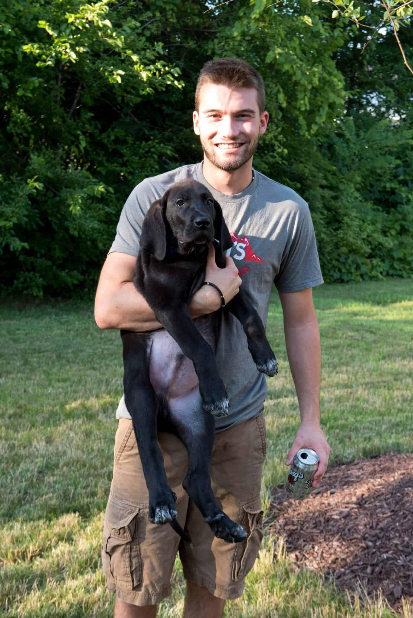 Apex employee holding Roman the black lab puppy