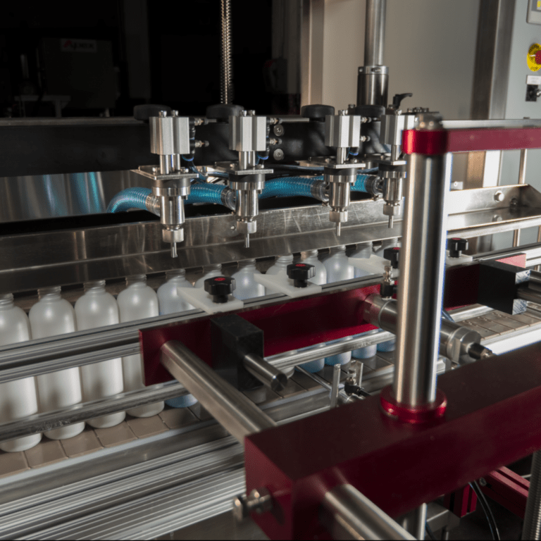 A 4 Head Pump Filler hovers over bottles on a conveyor ready to be filled